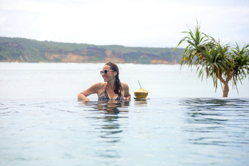 Indonesia, Lombok island, smiling woman in infinty pool