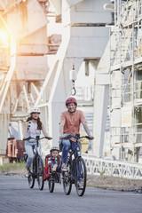Germany, Hamburg, family riding e-bikes at the harbor