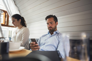 Mid adult businessman using smart phone by female colleague in office