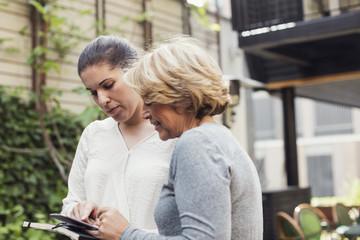Businesswomen using digital tablet together at office yard