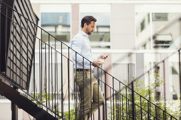 Side view of businessman using smart phone while moving down steps of log cabin