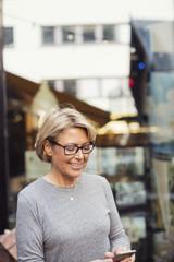 Woman using smartphone near street cafe