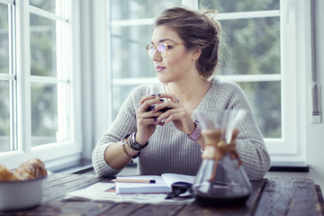Young woman drinking coffee at table  looking through window