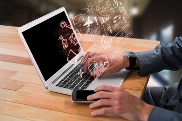 Composite image of cropped image of businessman using laptop