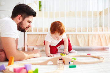 happy father playing with infant baby boy at sunny nursery room