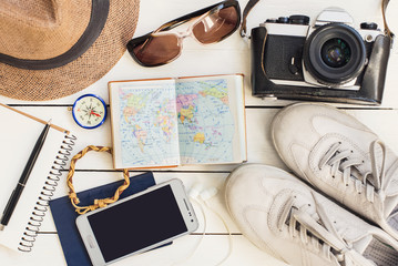 Accessories for travel. Different objects on wooden background. Passport, photo camera, smart phone, shoes, sunglasses and travel map. Top view. Hiking, holidays and tourism concept