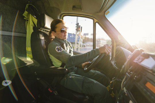 Side view of female paramedic driving ambulance on sunny day
