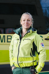 Portrait of confident paramedic standing with hands in pockets against ambulance