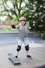 Smiling girl flexing muscles while standing on skateboard ramp