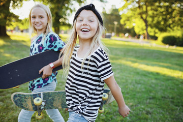 Portrait of happy friends carrying skateboards while walking on grassy field