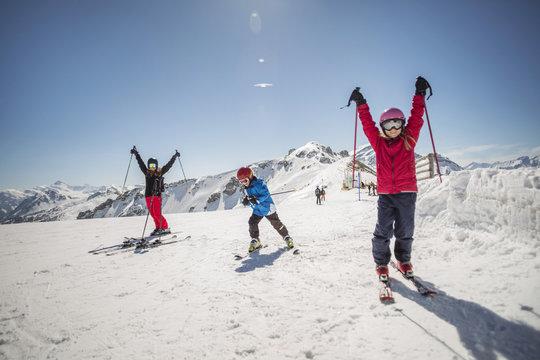 Full length of family enjoying while skiing against clear sky