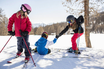 Family skiing on snow covered field