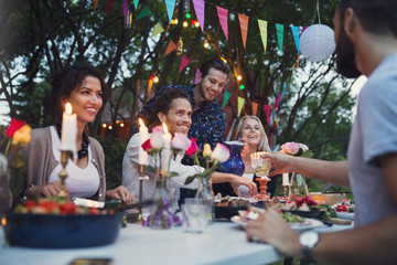 Multi-ethnic friends enjoying meal in back yard at garden party