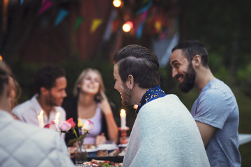 Happy friends enjoying dinner at garden party