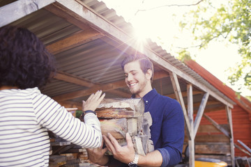 Rear view of woman giving logs to smiling male friend during sunny day
