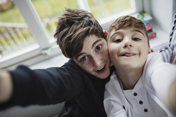 Portrait of happy brothers against window at home