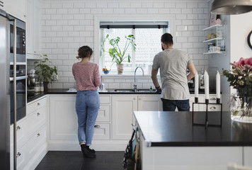 Rear view of couple working in kitchen at home