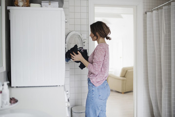 Side view of woman loading clothes in washing machine at home