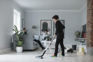 Boy vacuuming floor in living room at home