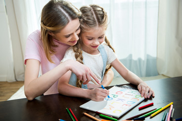 Smiling mother and daughter drawing colorful letters together
