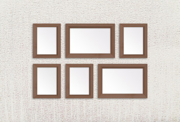 Six wooden photo frames on textured wallpaper background, interior decor mock up
