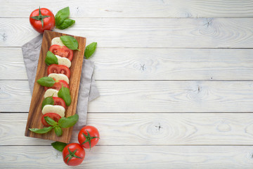 Mozzarella and tomato with basil leaves on a white wooden background