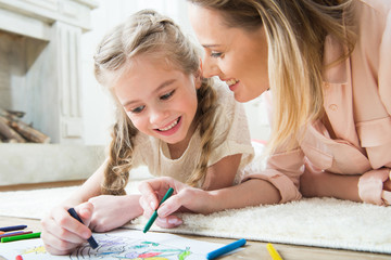 portrait of happy daughter drawing with mother at home