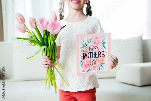 partial view of smiling girl holding tulips bouquet and postcard on mother's day holiday