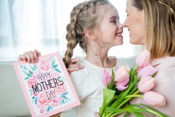 side view of smiling daughter greeting mother with tulips and postcard on mother's day
