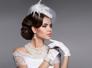 Retro woman portrait. Elegant lady with hairstyle, pearls jewelry set wears in hat and lace gloves posing isolated on studio gray background.