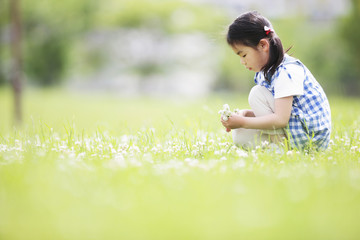 Girl Sitting on Grass Surrounded By Flowers