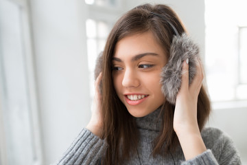Teen girl in fluffy headphones listen music