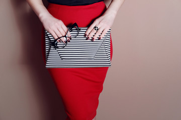 Wall Mural - Fashion woman in sexy red skirt with striped clutch bag. Close up