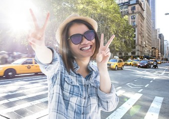 Composite image of Woman doing peace sign on street with flare