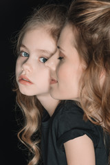 portrait of adorable daughter and mother, on black