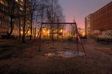 Empty swings on playground in poor city