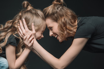 portrait of stylish daughter and mother smiling, touching foreheads and hugging on black