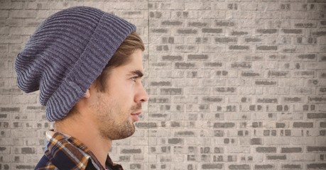 Composite image of Man with beanie against brick wall