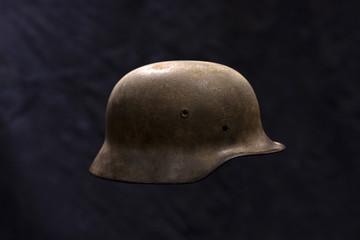 A rusty German World War Two military helmet on dark background
