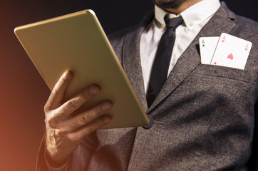Closeup of man, face not showing, holding tablet and two aces in pocket / poker concept