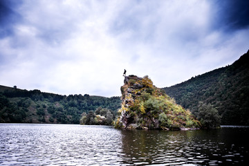 A rock surrounded by lake climbed by a traveller