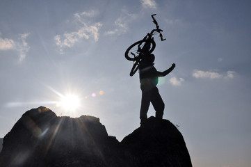 Silhouette the man with bicycle stand on top of the rock cliff mountain in sunset. Concept of successful man on top of the hill into the sun