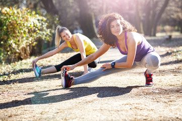 Two female friends stretching at the park after jogging.
