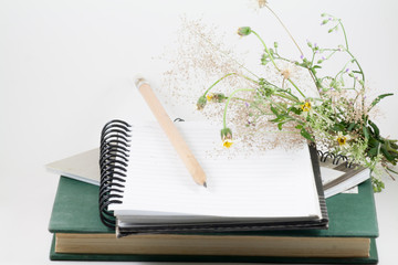 Flowers, pencil, book and a notebook on a desk.