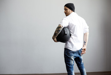 Rear view on tattooed body man in white shirt and black hat. Athletic biker looking back and holding blank black motorcycle helmet. Free space for advertising product and promotional text.