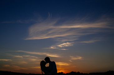 Silhouettes of a loving couple hugging at sunset