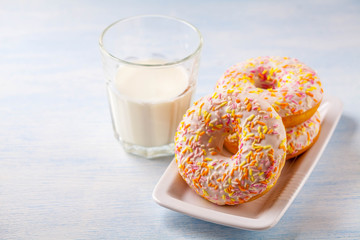 vanilla donuts with milk on a blue wooden background