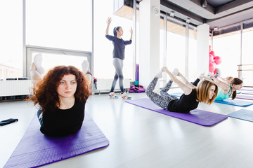 The trainer conducts stretching exercises for a group of girls