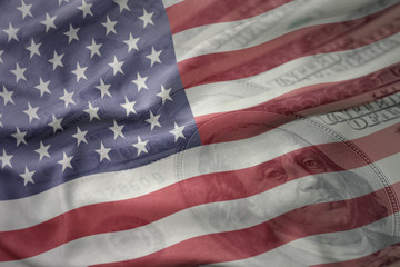 colorful waving national flag of united states of america on a american dollar money background. finance concept