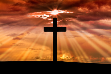 Jesus Christ wooden cross on a scene with dark red orange sunset, twilight light in the background, dramatic sky, clouds, sun rays, sunbeams. Christian Easter, resurrection,Good Friday concept